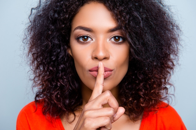 Shh! Closeup portrait of mysterious charming woman with modern hairdo asking for keeping silence holding forefinger on plump lips isolated on grey background